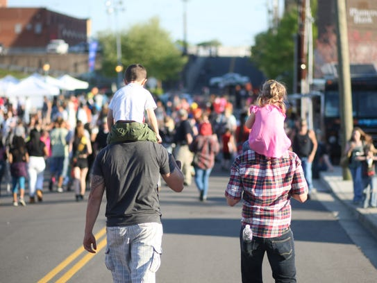 Two young Rivers & Spires attendees get a piggyback