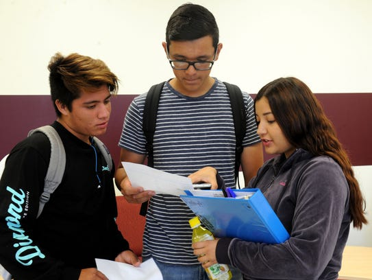 Eric Blanco, from left, Luis Buenrostro and Mariana Garcia share their class schedules at Conejo Valley High School's first day of classes. The alternative high school opened in a new facility.