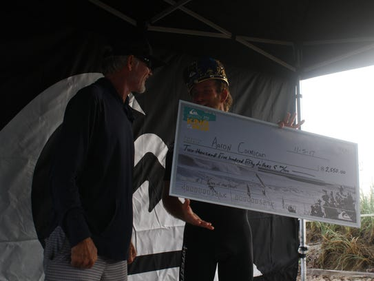 A check is presented to surfer Aaron Cormican from