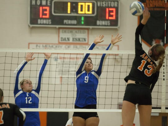 Armada senior Brittany Maxwell spikes the ball as Cros-Lex sophomore Rebecca Oden and senior Brooke Smith attempt to block during a volleyball game Tuesday, Oct. 28, 2014 at Armada High School.