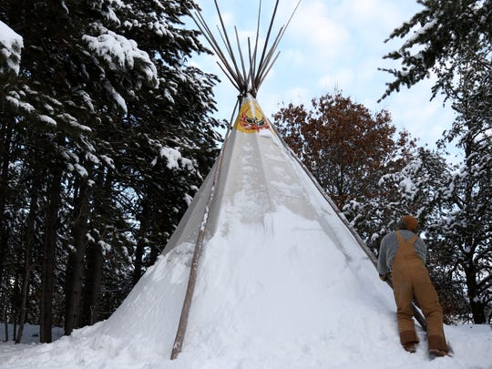 Paul Priestley, 29, begins creating ventilation through the deep snow outside his 20-foot teepee, constructed out of 15-ounce marine canvas, after returning for the spring semester of his final year as a student at UWSP. This is Priestley's third winter living in the teepee: isolated from electricity, running water and the rest of the world.