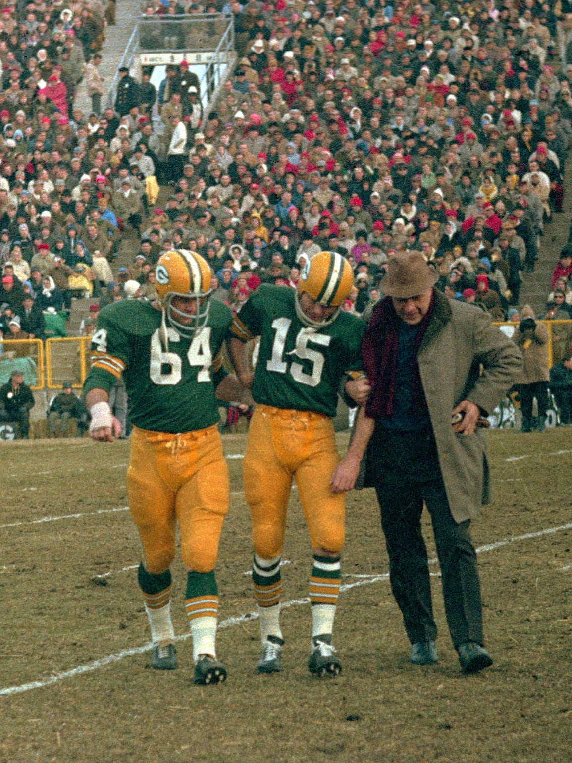 Green Bay Packers quarterback Bart Starr (15) is helped