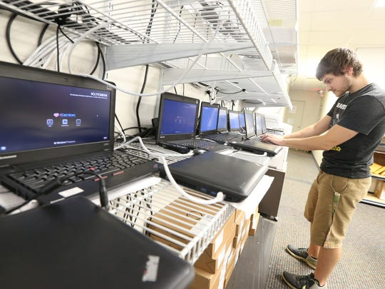 Zach Fabiano, field operations specialist, prepares laptops for deployment in clinical trials at iCardiac Technologies.