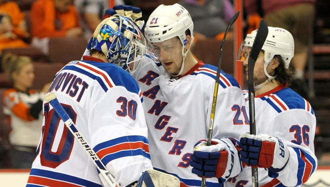 New York Rangers goalie Henrik Lundqvist (30) celebrates with center Derek Stepan (21) and right wing Mats Zuccarello (36) after defeating the Philadelphia Flyers 4-1 in game three of the first round of the 2014 Stanley Cup Playoffs at Wells Fargo Center.
