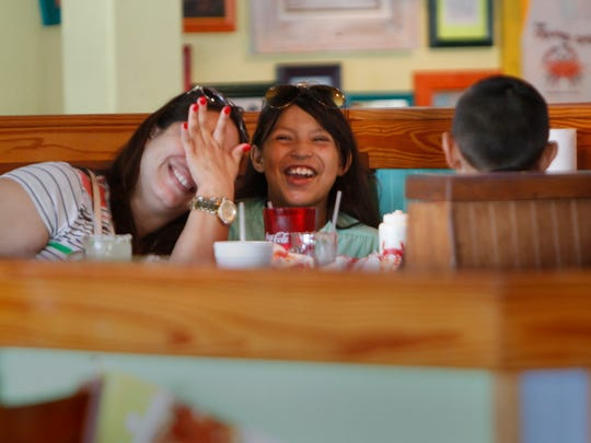 Nina Martinez and Gabriela Barnhart share a laugh while eating lunch at Pincher's Crab Shack in the Gulf Coast Town Center in Fort Myers Wednesday.