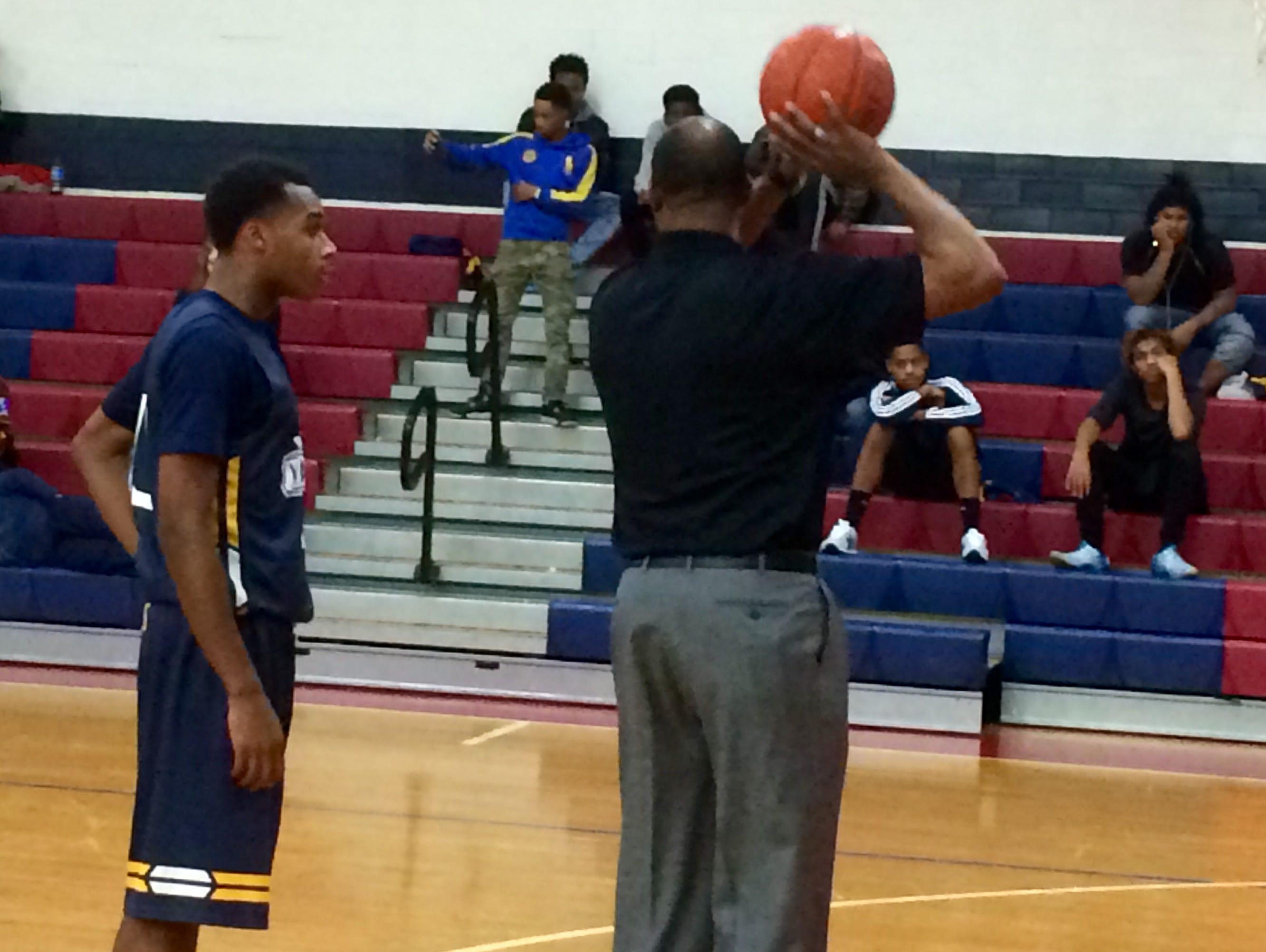 Coach Derrick Fooks offers some instruction to Leander Roberts during halftime.