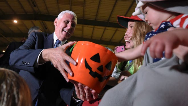 Republican vice president candidate, Gov. Mike Pence hands out candy while greeting supporters during a rally in Clearwater, Fla., Monday, Oct. 31, 2016.
