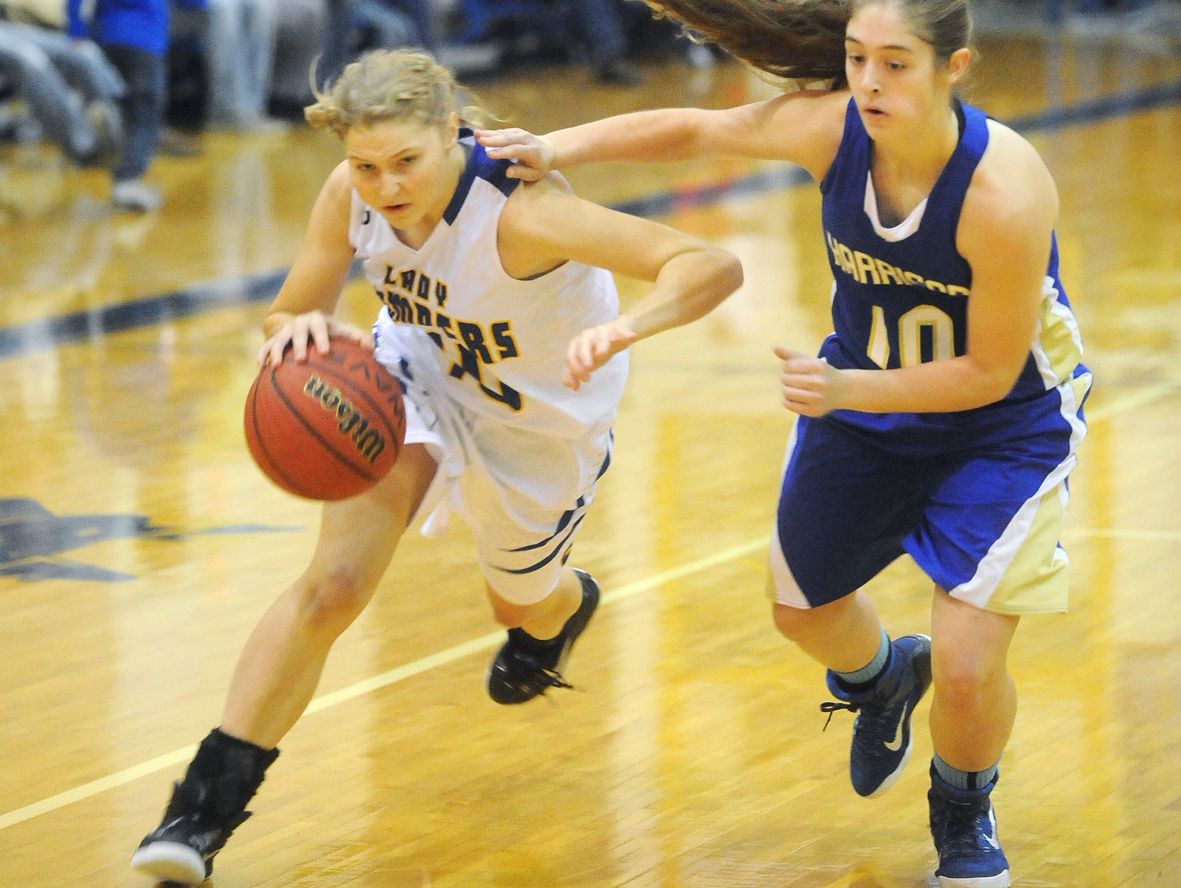 Mountain Home's Sydney Blevins, left, drives past a Harrison player during a game earlier this season. The Lady Bombers traveled to Jonesboro and fell 50-31 to the Lady Hurricane on Friday night.
