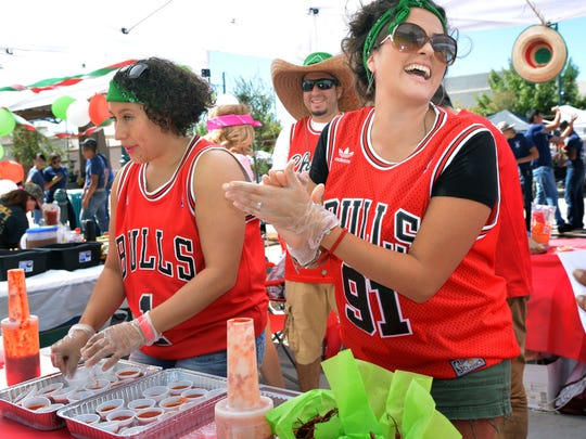 """Sylvia Flores, left, prepares samples of last year's winner """"Los Pica Chiles"""" salsa Sunday as Diana Diaz claps for a patron who voted for their chile at this year's fest."""