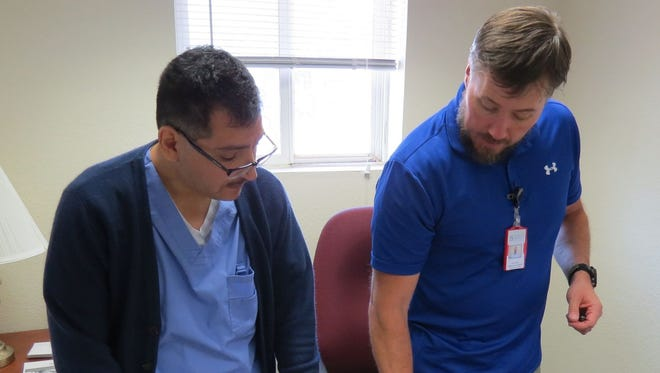 Erik Larson, NP (right), and Albert Trevino, RN (left), discuss medication indications and dosing guidelines for a client at Community Reach Center, at the Thornton, Colorado, location of the community-based mental health organization.