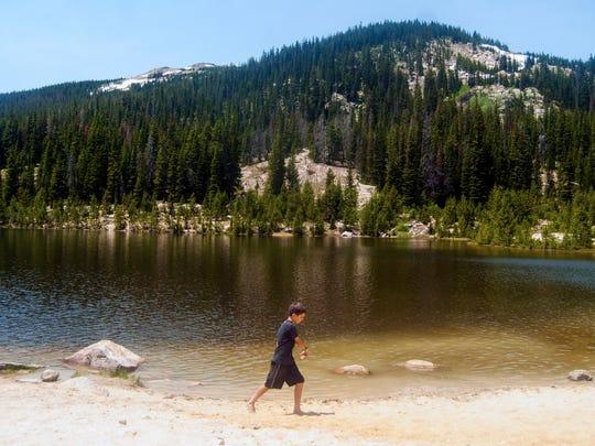 A Boy Scouts member walks across the beach at Sandbeach Lake in Rocky Mountain National Park.