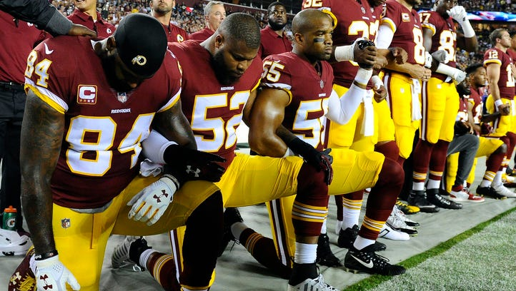 Washington Redskins players kneel before a game last