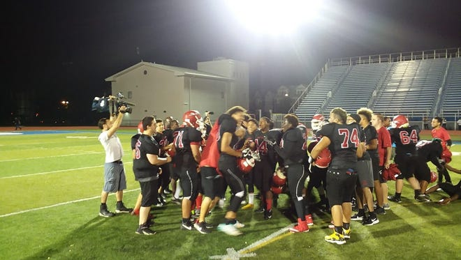 Newark East Side players celebrate after an exciting 32-30 win over Belleville snapped a 55-game losing streak.