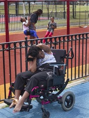 Yesenia Parker sits alone as her sisters and cousin play on the swings at Audubon Park in Jersey City. Yesenia Parker of Camden was shot by her father and left paralyzed having only limited use of her arms and hands. Despite of all the difficulties, Shandar Parker is determined to make a stable life for her daugher, and has set up a GoFundMepage to appeal for help.