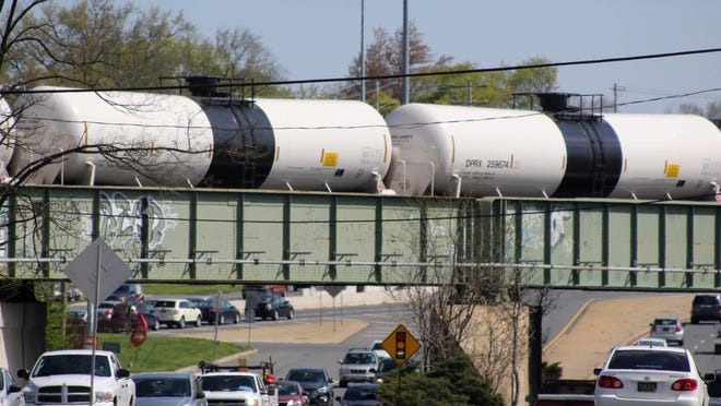 Crude oil tank cars linger on a rail bridge while traffic passes underneath at the US 13/40 split, along the northern end of a siding where Norfolk Southern crude oil trains sometimes idle for hours at a stretch.