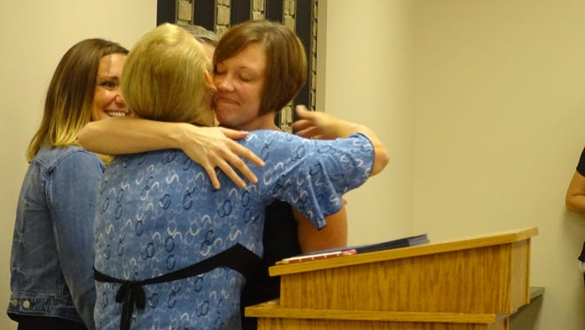 A drug court graduate shares a hug with Kim Romoser, probation officer for treatment court. Twenty-eight people graduated from the year-long program Wednesday.