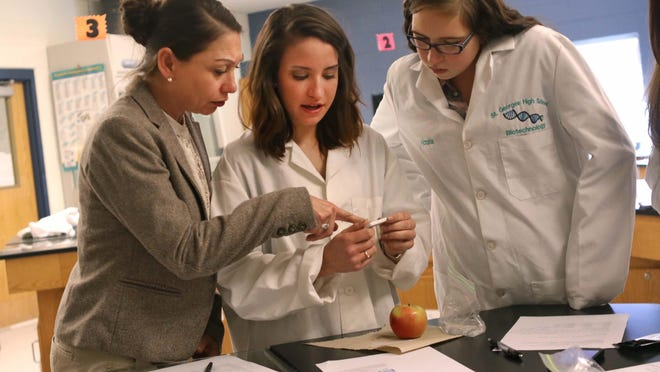 Left to right Biotechnology teacher Danya Espadas at St. Georges High School reassures the result that Sadie Sanclemente , 17, and Victoria Graden, 17, both seniors, got from testing an apple for pesticides during class.