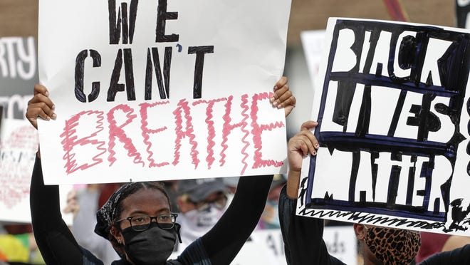 Protesters hold signs during a protest over the death of George Floyd,Tuesday, June 2, 2020, in Orlando. Floyd died after being restrained by Minneapolis police officers on May 25.
