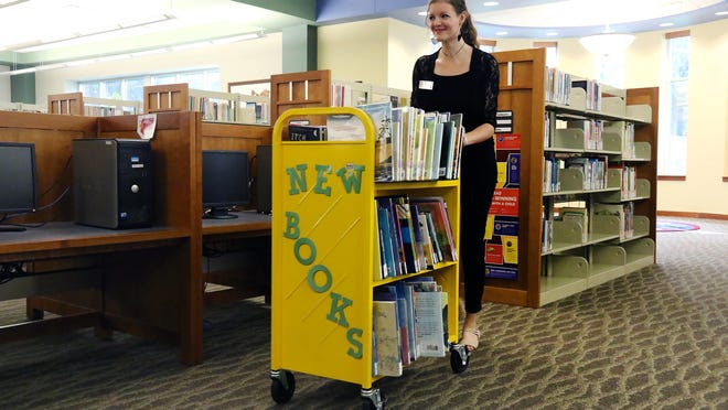 Leah Wineland, Fort Smith library teen specialist, pushes a cart of new books offered at the Fort Smith Main Library.