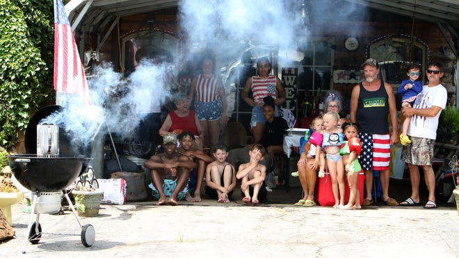 Members of the Ed and Elizabeth Williams family are joined by friends, Saturday, July 4, 2020, for barbecue and swimming at Ed's Car Farm in Hackett to celebrate Independence Day,