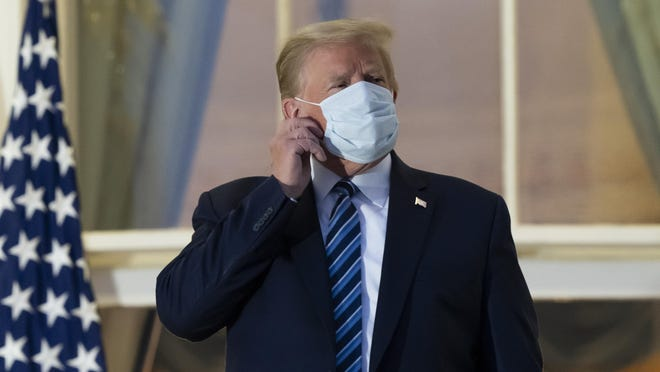 President Donald Trump removes his mask as he stands on the Blue Room Balcony upon returning to the White House Monday.