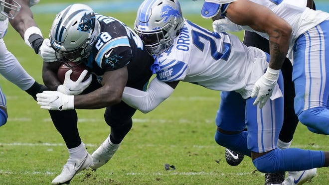 Carolina Panthers running back Mike Davis is tackled by Detroit Lions cornerback Amani Oruwariye during the second half of an NFL football game Sunday, Nov. 22, 2020, in Charlotte, N.C.