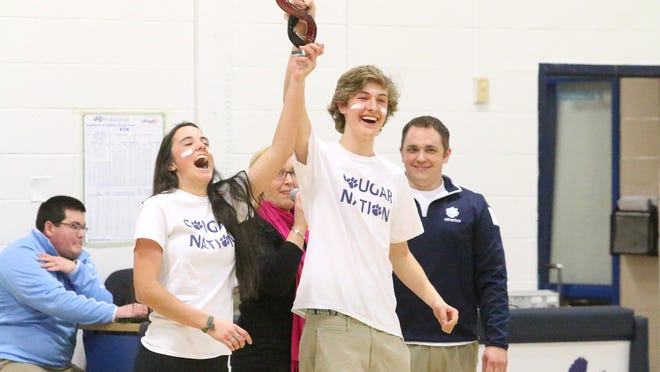 Mount Mansfield Union juniors receive the Competitive Giving League winners' trophy on Feb. 16. Kristin Kany, CGL founder, is in the middle, and MMU Athletic Director David Marlow is on the right.