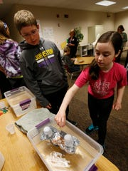 Sarah Linder, 11 (right), places pennies into her and Hank Lucas' boat as they test to see how much their foil watercraft will carry during a Makers Fair on March 24 at Beaver Creek Elementary in Johnston.