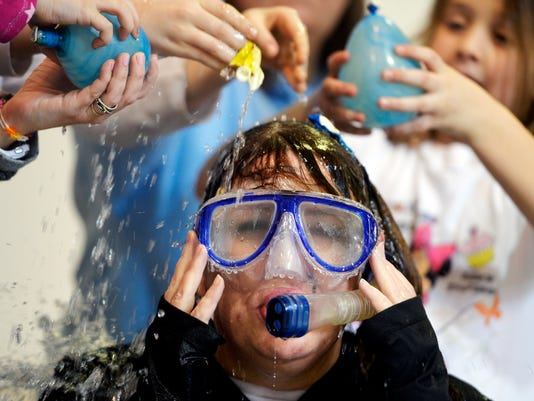 Fairview Elementary students pop and squeeze water balloons over principal Julie Dougherty's head during a pep rally on Friday, Feb. 7, 2014. Students at Fairview Elementary in Fairview Township raised $5,082.50 in the five weeks since 2014 began to benefit the West Shore Hope Express and the Four Diamonds Fund. To celebrate raising awareness of pediatric cancer as well as funds to counteract it, students popped 60 water balloons over principal Julie Dougherty's head. Chris Dunn -- Daily Record/Sunday News
