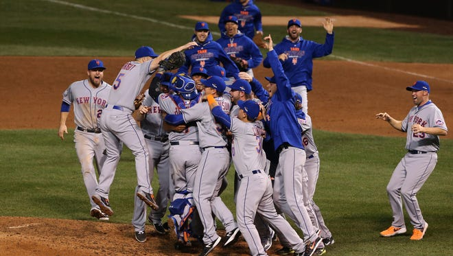 New York Mets players celebrate on the field after defeating the Chicago Cubs in Game 4 of the NLCS at Wrigley Field.