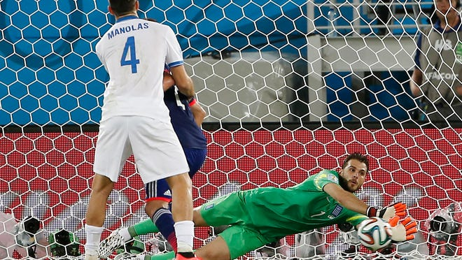 Greece goalkeeper Orestis Karnezis makes a save against Japan as Greece defender Kostas Manolas (4) looks on during the second half of their 0-0 tie in a World Cup match on Thursday.
