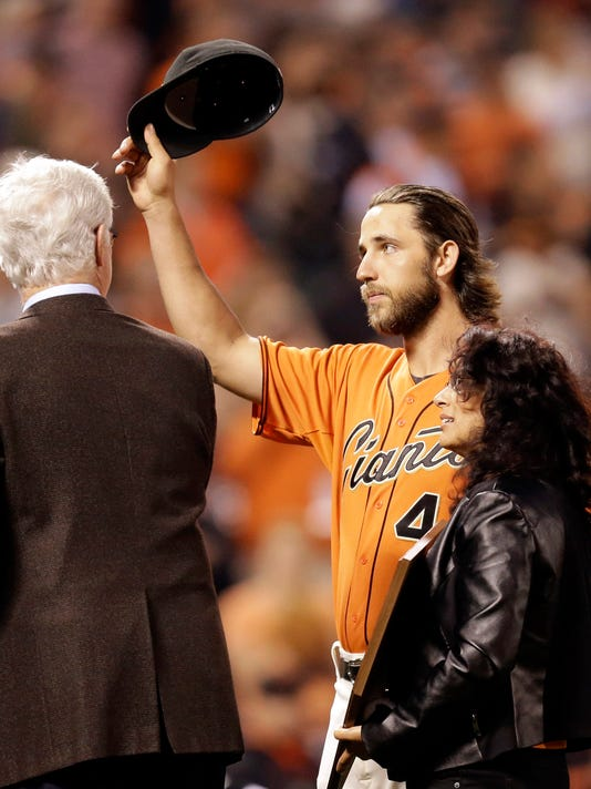 San Francisco Giants' Madison Bumgarner tips his hat to fans after being named the 2014 recipient of the Willie Mac Award prior to a baseball game against the San Diego Padres, Friday, Sept. 26, 2014, in San Francisco. At right is Allison McCovey, at left, Giants announcer Mike Krukow. (AP Photo/Ben Margot)
