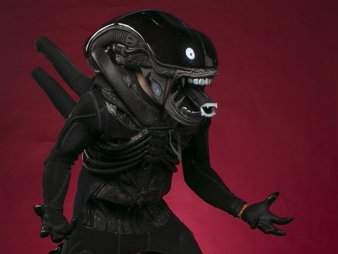 A cosplayer dressed as the Alien poses for a photo