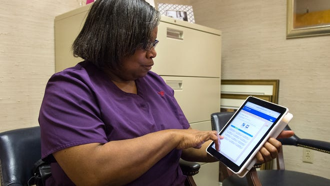Sharon Gourdine tries out St. Francis' new online portal at the Woodward Medical Center in Greenville on Monday, July 25, 2016. The portal allows patients to use a mobile device to ask physicians questions, look up lab results, or book appointments without having to call.