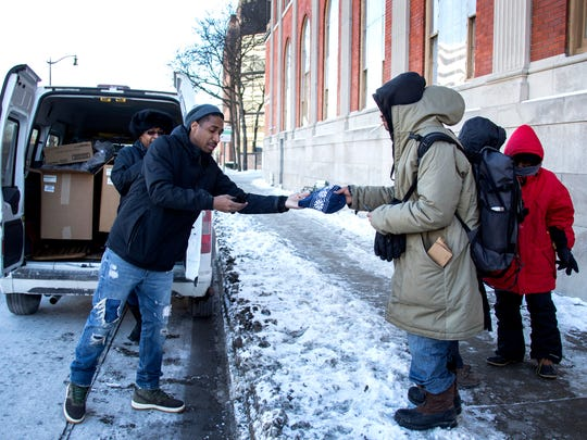 Antonio Camak, 28, of Detroit, left, who works for Cass Community Services, hands a new hat to Milton Murray, 52, who is homeless, outside of the Pope Francis Center St. Peter & Paul Jesuit Church in Detroit Friday Jan. 5, 2018.