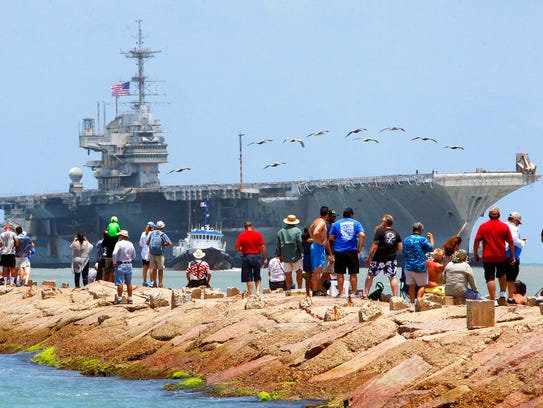 People line the jetties as they watch the USS Independence