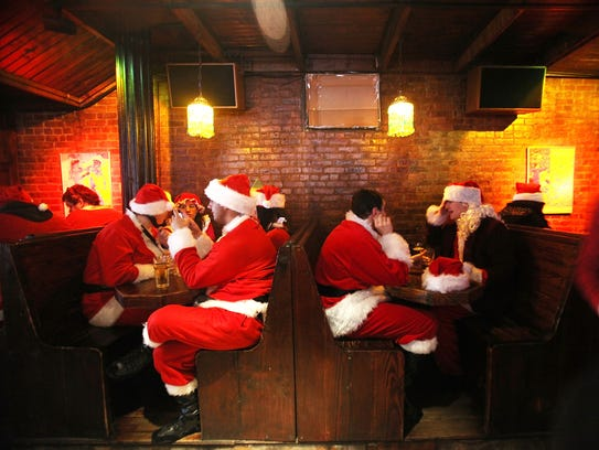 Revelers dressed as Santa Claus celebrate during the