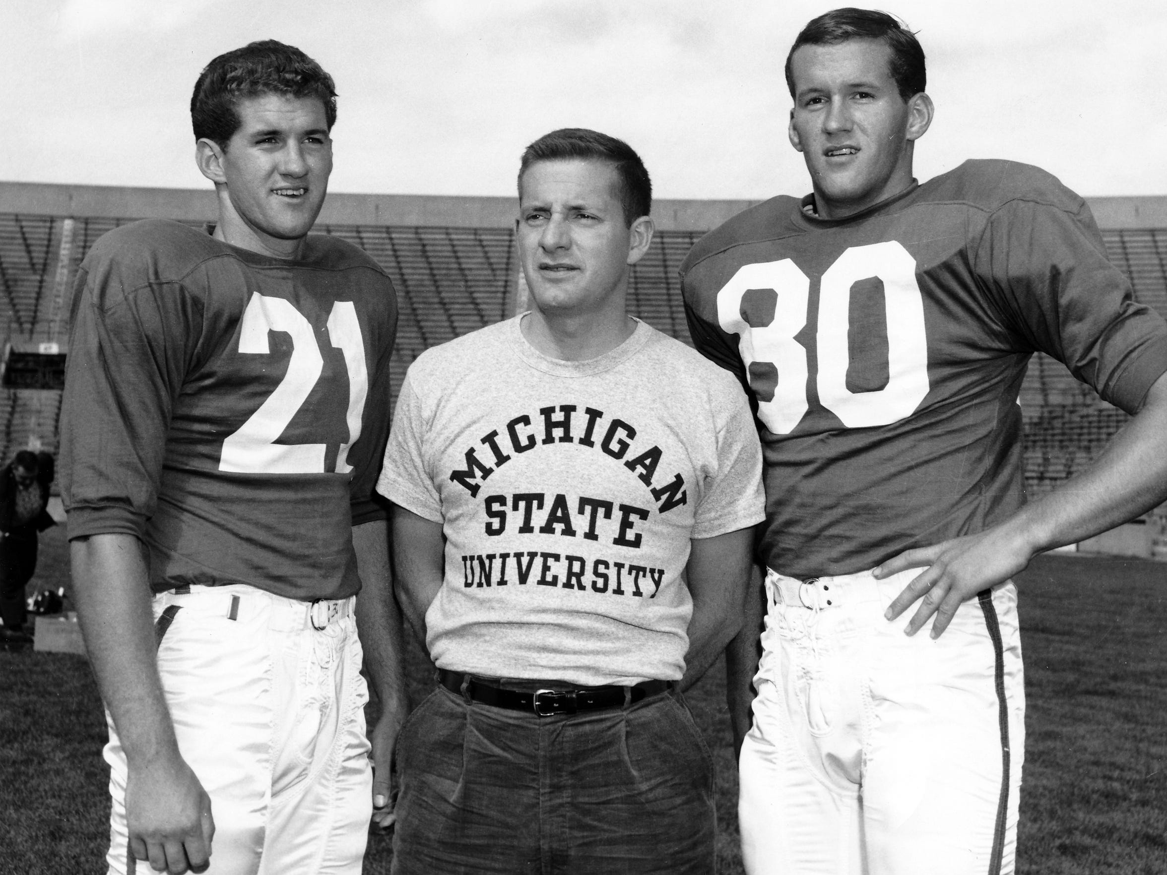 Michigan State University quarterback Dick Proebstle, left, appears with assistant coach John McVay, middle, and his younger brother and teammate Jim Proebstle. Jim wrote a 2015 book exploring the behavioral and other problems caused by Dick's chronic traumatic encephalopathy, which was likely due to head injuries sustained while playing football.