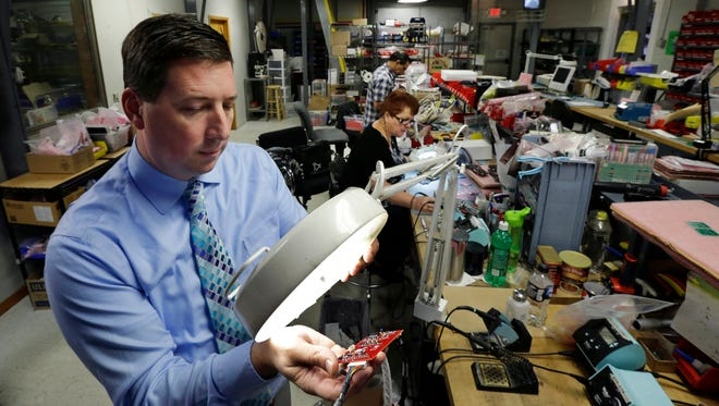 Berkeley Varitronic Systems' CEO Scott Schober uses a magnifier to look at a circuit board for a cellular telephone detector.