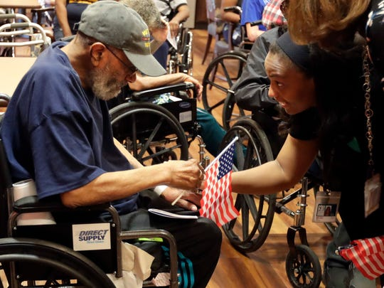 """Alton Presley, left, receives a flag in recognition of his service from Melissa Kirksey at Seasons Hospice & Palliative Care organized a  """"We Honor Veterans"""" day to give pins and certificates to veterans they are caring for at The Villa at Bradley Estates."""