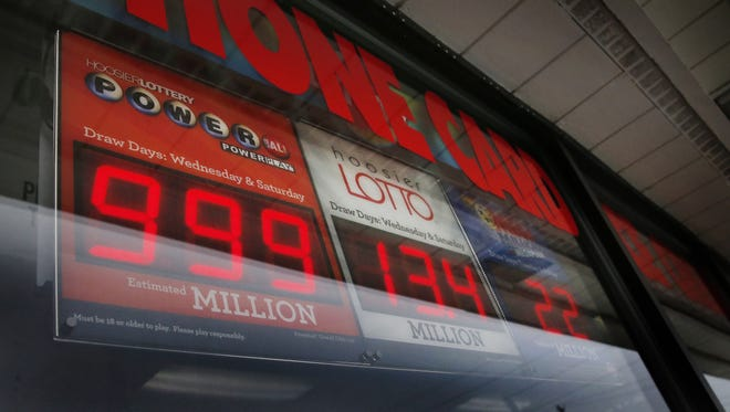 A Powerball lottery sign sits in the window of the Phillips 66 gas station on East Street on Jan. 13, 2016.