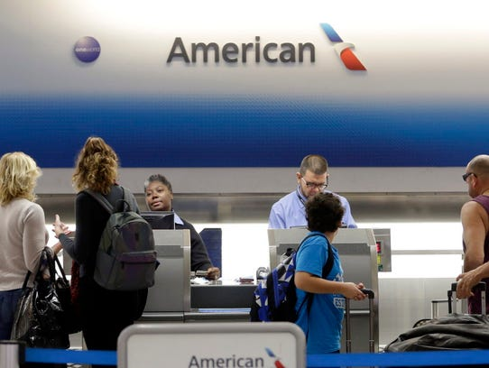 Passengers check in their luggage at the counter at