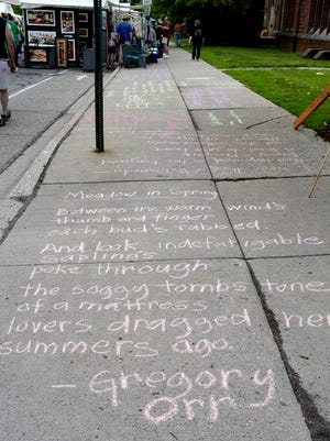 Poetry was chalked on the sidewalk is on display at the East Lansing Art Festival Saturday in 2015. Lansing is looking for its first poet laureate to promote the written and spoken word in Ingham, Eaton and Clinton counties.