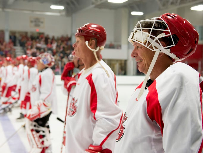 Red Wings general manager Ken Holland, right, and the rest of the white team line up for the national anthem before the start of a game of Red Wings alumni and local celebrities at Centre Ice Arena in Traverse City on Saturday, Sept. 20, 2014.