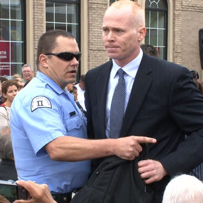 Jim Keady, Spring Lake, is escorted away after he heckled