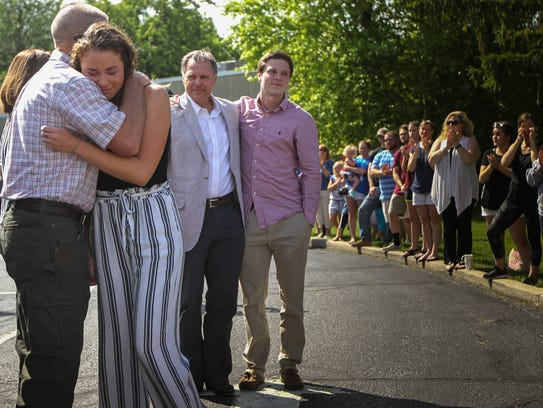 Greta Warmbier is embraced by a community member while