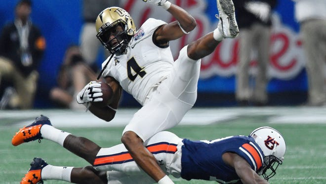 Auburn defensive back Javaris Davis (13) tackles Central Florida wide receiver Tre'Quan Smith (4) during the first half of the Peach Bowl NCAA college football game, Monday, Jan. 1, 2018, in Atlanta. (AP Photo/Mike Stewart)