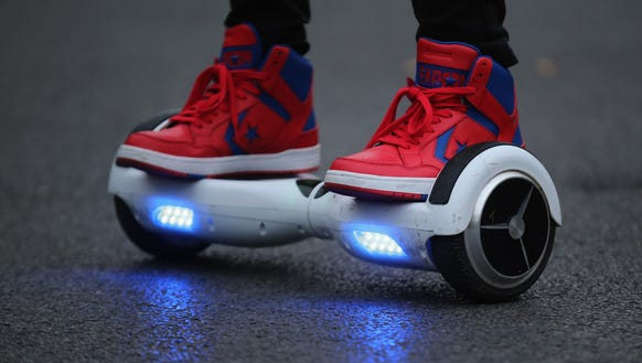 A youth rides a hoverboard, which are also known as