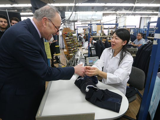 U.S. Senator Charles Schumer greets Hickey Freeman seamstress Chin Nguyen during his visit to help announce about 50 new jobs at the Rochester clothing company.
