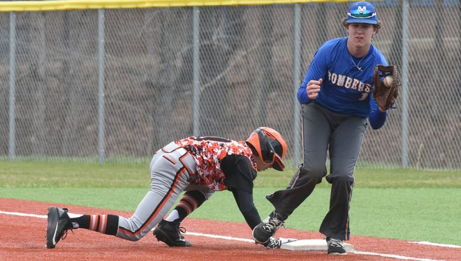 Viola's Gage Harris dives back into first base as Mountain Home's Trey Jordan takes a pick-off throw during action Tuesday at McClain Park.